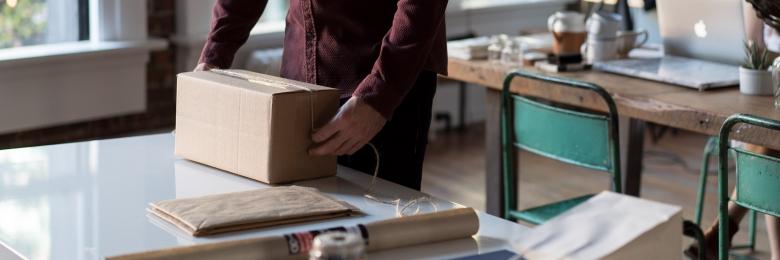 A man putting tape on a box