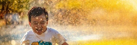 Kid running through a sprinkler